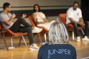 photo of emerging writer, in a juniper tee shirt, listening to Q&A